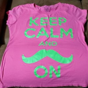 pink shirt with green mustache and words